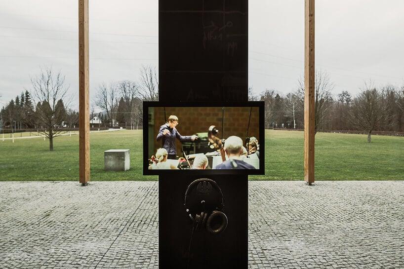 stanowisko ztelewizorem isłuchawkami na tle widoku na rozległy ogród projektu Nizio Design International