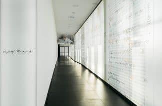 biały korytarz z czarną podłogą ze ścianą wyłożoną powiększonymi zapisami nutowymi Krzysztofa Pendereckiego projektu Nizio Design International
