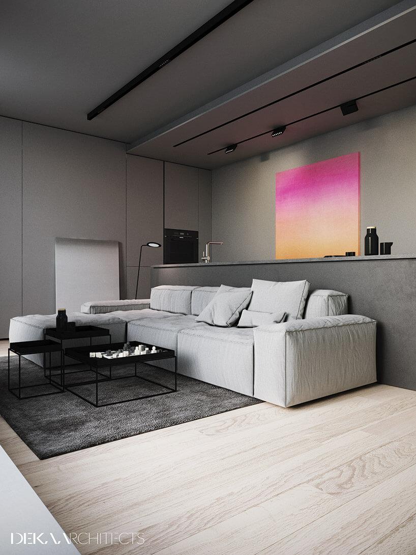 szary salon zdużą białą sofą czarnym stolikiem