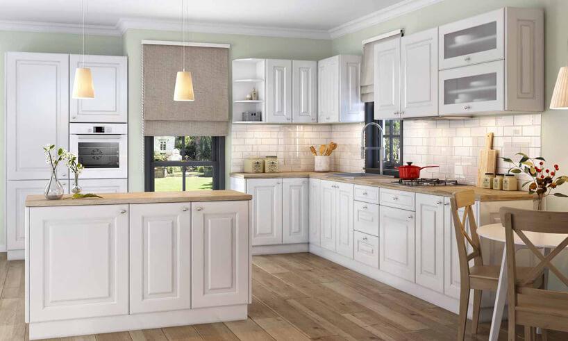 biała duża kuchnia wstylu prowansalskim zbiałym frontami szafek imałą wyspą kuchenną zdrewnianymi blatami