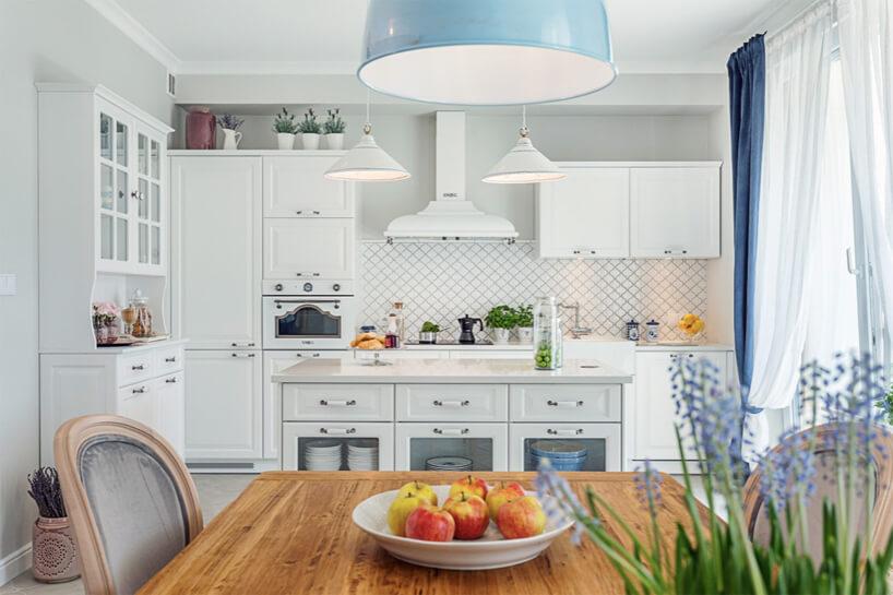 biała kuchnia wstylu prowansalskim zbiałym frontami niektórymi jak tło dla stołu drewnianym blatem