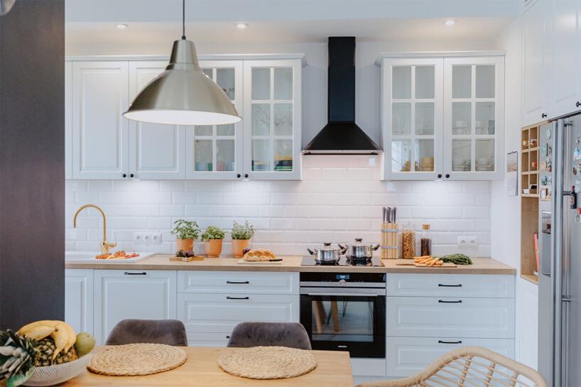 biała kuchnia wstylu prowansalskim zpłytkami wkształcie cegiełki zdrewnianym blatem iczarnym wyciągiem oraz kuchnią