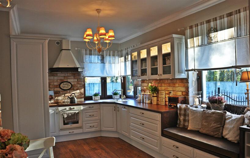 kuchnia wstylu prowansalskim zbiałymi frontami ścianami zceglanymi wstawkami zciemnym drewnianym blatem zsiedziskiem przy dużym oknie na końcu blatu kuchennego