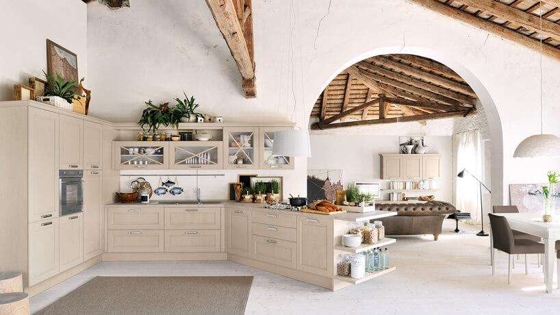 przestronna biała kuchnia wstylu prowansalskim zkremowymi szafkami zwyspą pod skosem pod drewnianymi starymi filarami na tle wejścia do salonu