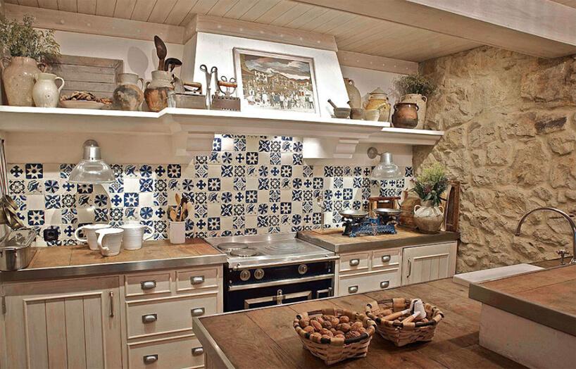 kuchnia wstylu prowansalskim zkamienną ścianą izbiało niebieskimi małymi płytkami nad drewnianym blatem zdesek wykończoych