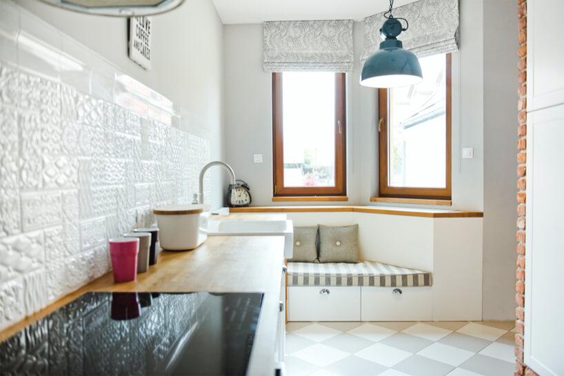 nowoczesna biała kuchnia zfakturowanymi białymi płytkami nad drewnianym blatem kuchennym na tle siedziska pod dwoma wąskimi oknami