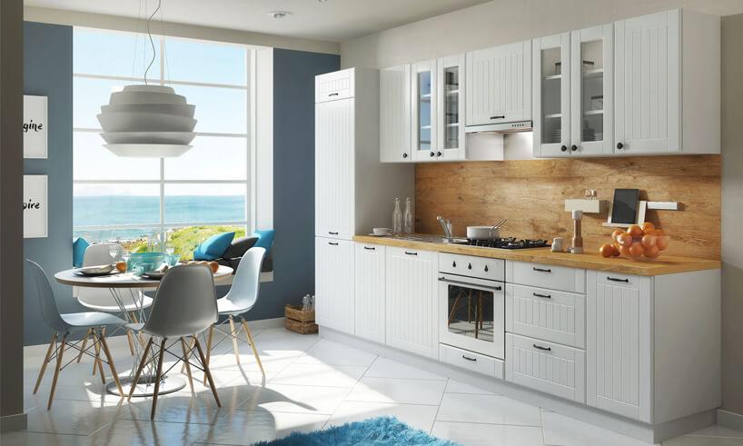 nowoczesna kuchnia wstylu prowansalskim zbiałym frontami zdrewnianym blatem pod ścianą zpłytkami wstylu drewna obok niebieskiej ściany zdużym oknem zwidokiem na morze
