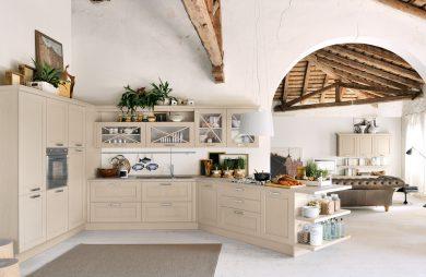 przestronna biała kuchnia w stylu prowansalskim z kremowymi szafkami z wyspą pod skosem pod drewnianymi starymi filarami na tle wejścia do salonu