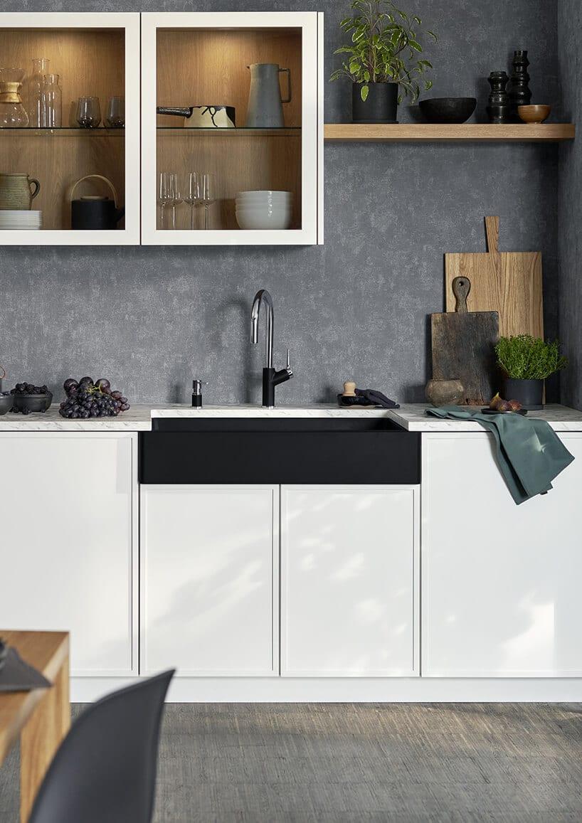 ciemny zlewozmywak pod blatowy wkuchni zfrezami oraz białym kolorem iciemno szarymi betonowymi ścianami