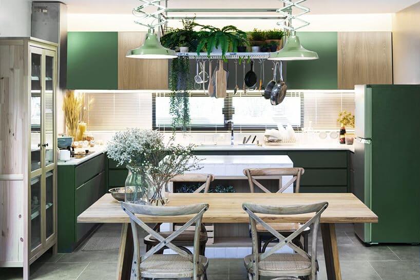 zielone wnętrze kuchni zdużym prostokątnym stołem nad którym wisi lampa zzielonymi roślinami