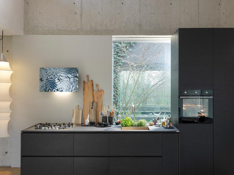 kuchnia zciemnymi szafkami idużym oknem