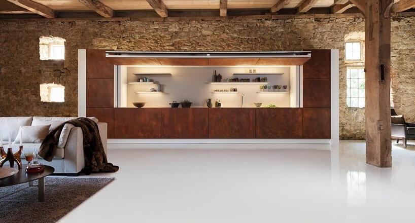aneks kuchenny schowany za brązowym frontem wkamiennej rezydencji zdrewnianymi kolumnami