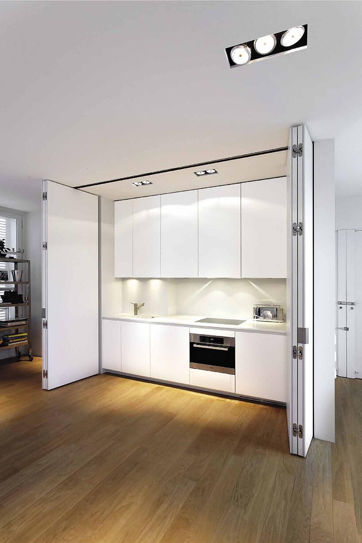 biały aneks kuchenny chowany za białymi składanymi drzwiami