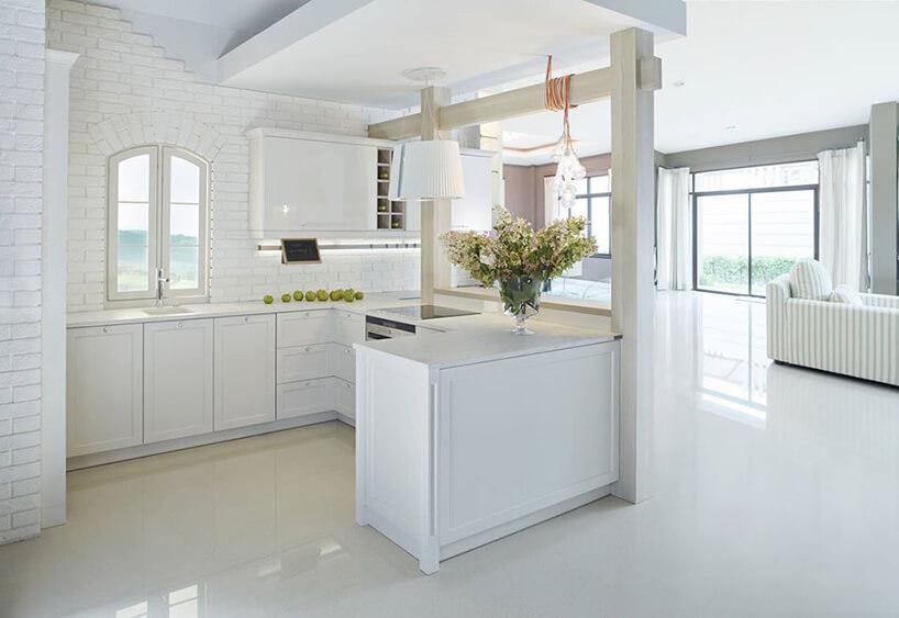 biała kuchnia zbiała cegłą przy drewnianych belkach