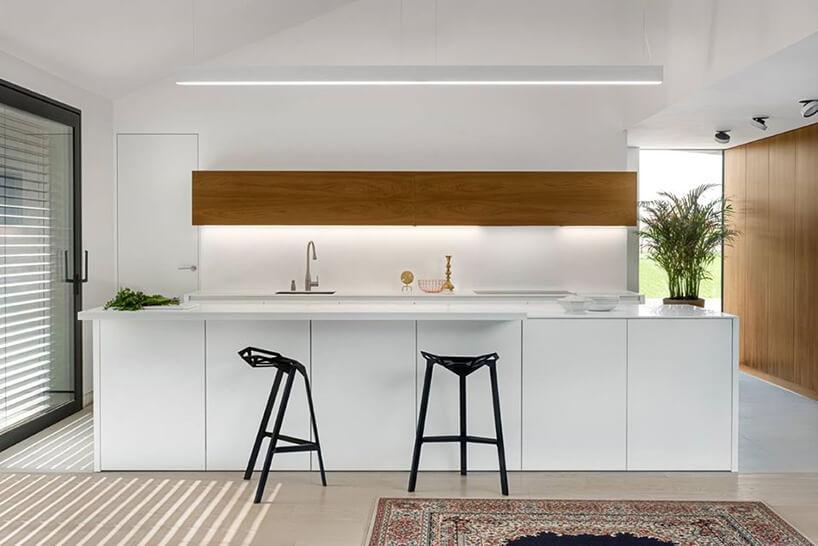 biała kuchnia zdużą wyspą zwysuniętym blatem idwoma czarnymi krzesłami