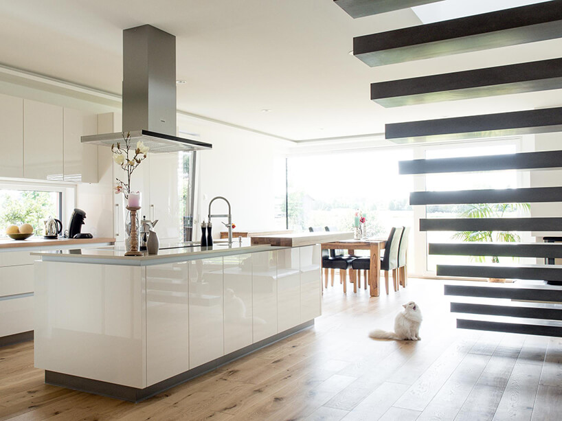 jadalnie połączona znowoczesną kuchnią zbiałym błyszczącymi frontami idużą wyspą kuchenną obok ciemnych schodów