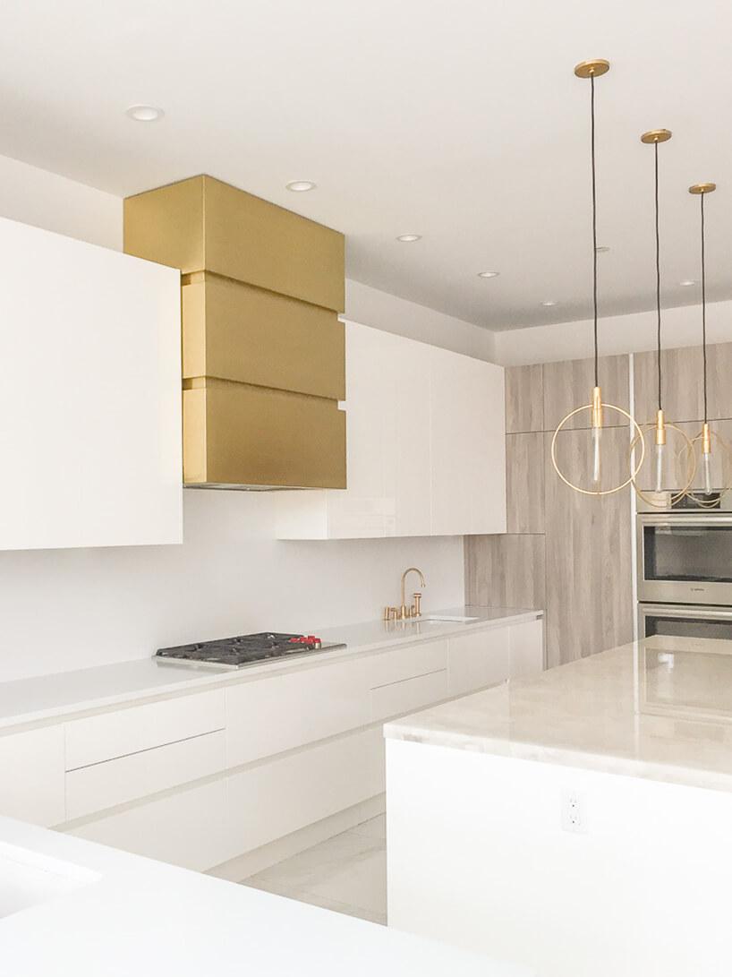 biała nowoczesna kuchnia ze złotym okapem zbiała wyspą zkamiennym blatem