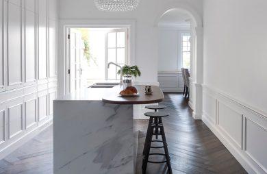 biała kuchnia z ciemną podłogą i centralną wyspą z białego kamienia