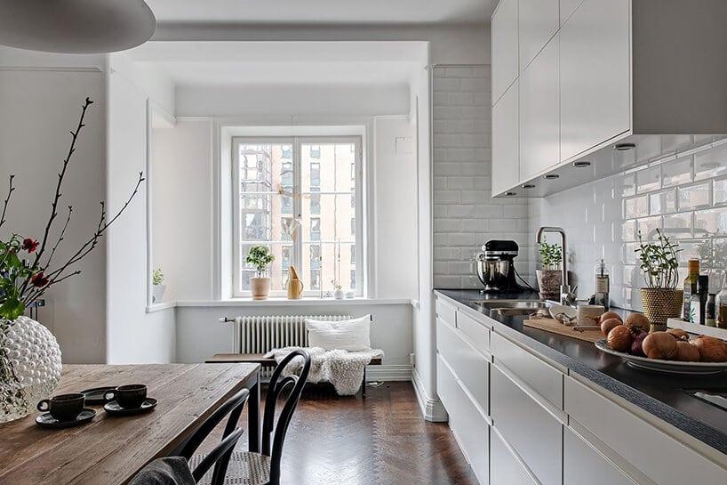 biała kuchnia zbiałymi szafkami ciemno szarym blatem obok dużego drewnianego stołu