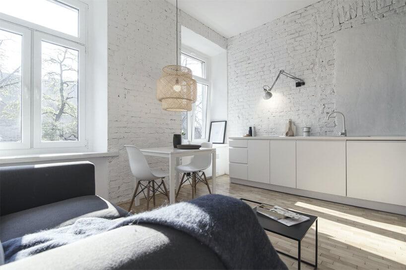 biały aneks kuchenny wkawalerce bez górnych szafek na tle ceglanej ściany pomalowanej na biało