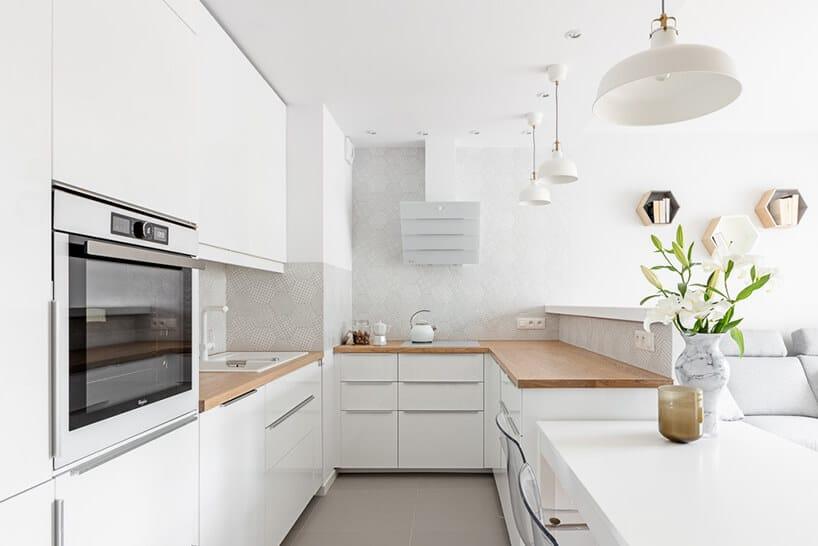 biała kuchnia zdrewnianym blatem pomiędzy białymi błyszczącymi frontami szafek