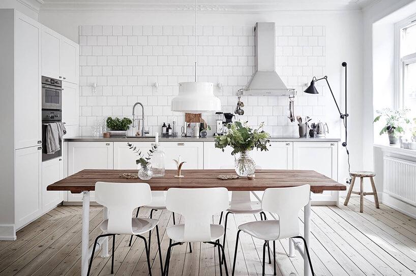 biała kuchnia zszarym blatem jako tło dla stołu zbrązowym olejonym drewnianym blatem