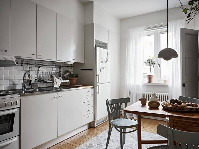 biała kuchnia zdrewnianą podłogą imałym drewnianym stolikiem