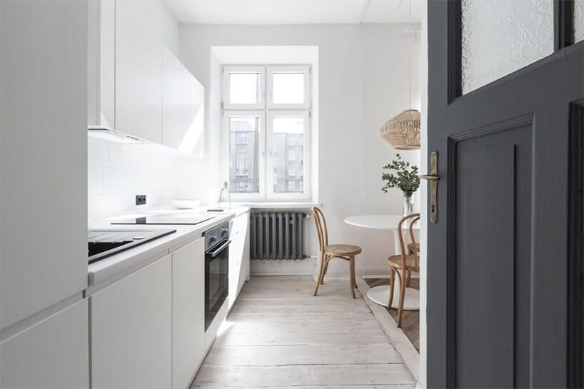 biała kuchnia zbiałym okrągłym stolikiem zdwoma brązowymi krzesłami obok szarego kaloryfera pod oknem