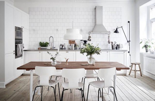 biała kuchnia z szarym blatem jako tło dla stołu z brązowym olejonym drewnianym blatem
