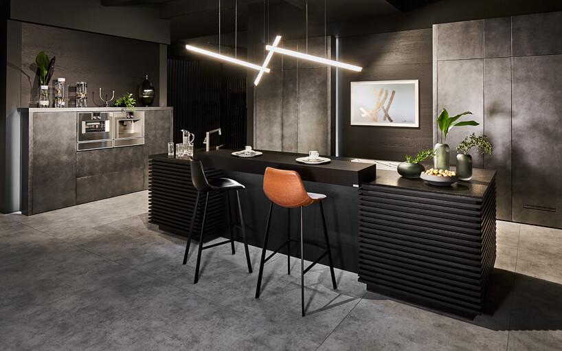 Modne kolory wkuchni brązowe iczarne krzesło na tle czarnego blatu ze zlewozmywakiem