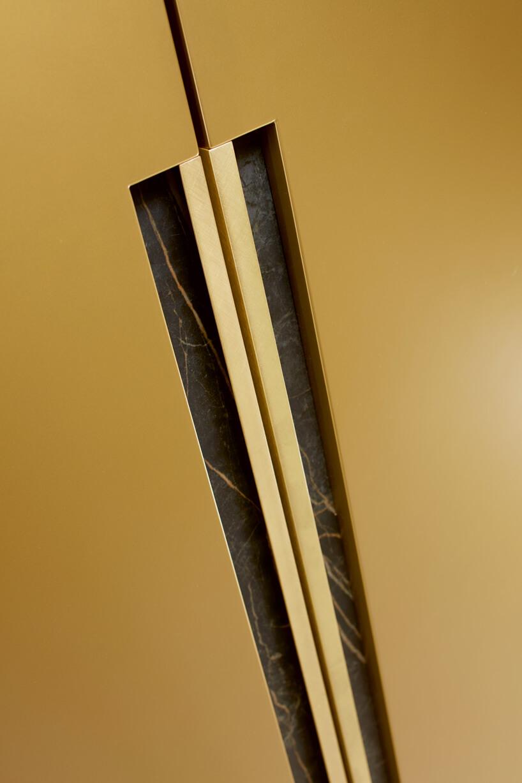 Metaliczne kolory wkuchnibrązowe drzwi do szafki zmarmurowym ozdobieniem