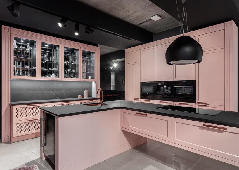 różowa kuchnia wpastelowym odcieniu zdużą wyspą kuchenną