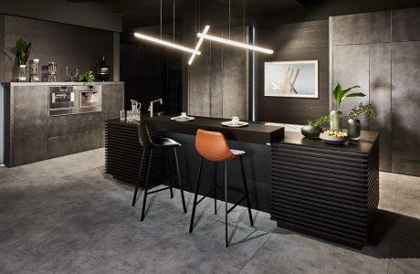 brązowe i czarne krzesło na tle czarnego blatu ze zlewozmywakiem