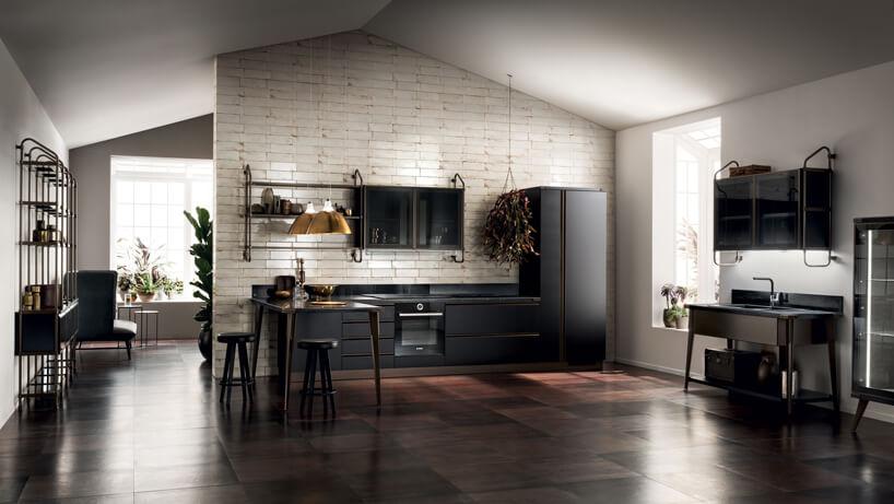 duża kuchnia zciemnymi meblami na tle beżowej ściany iciemno brązowej podłogi