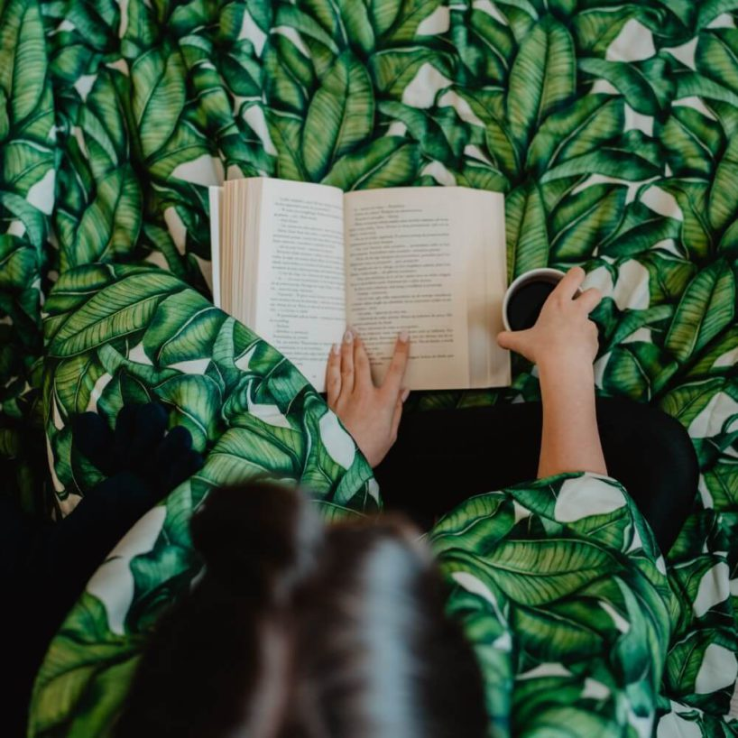 pościel wliście tropikalne zkobietą czytającą książkę ikawą