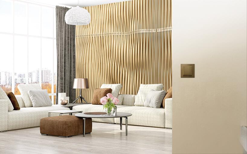 złoty włącznik na ścianie weleganckim salonie ze złotą ścianą