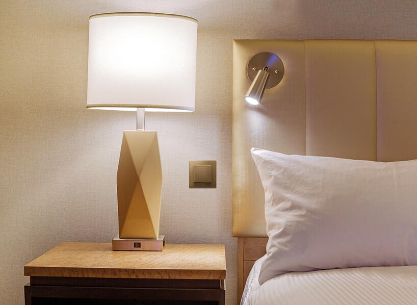 złoty łącznik Sky Niessen od ABB przy łóżku wsypialni