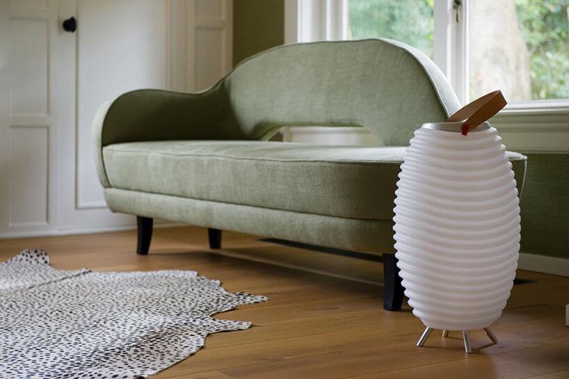 zielona nowoczesna kanapa na czarnych nogach przy białej lampie