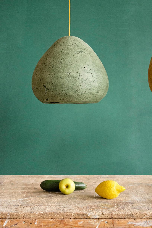 szara bulwiasta lampa wisząca nad starym stołem
