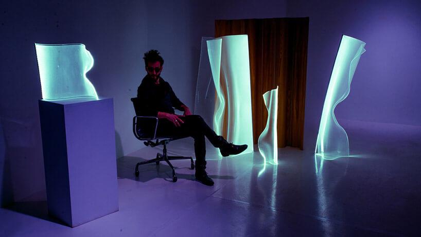 mężczyzna siedzący na fotelu pośród nietypowych lamp