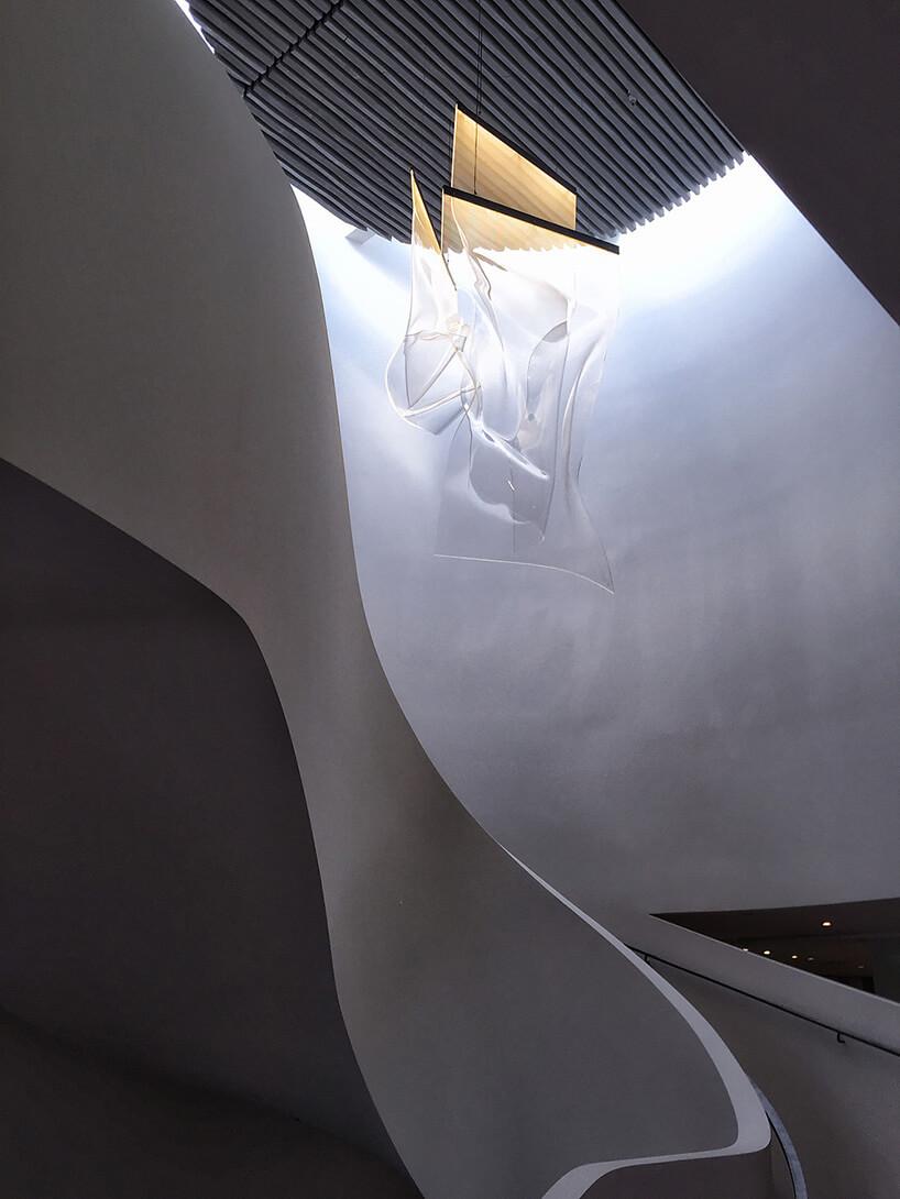 lampy zwygiętych paneli wiszące nad szarymi schodami