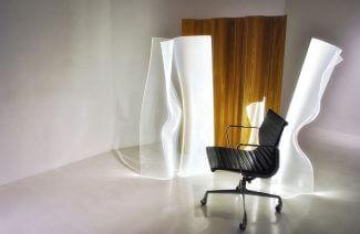 fotelem biurowy na tle lamp z wygiętych paneli