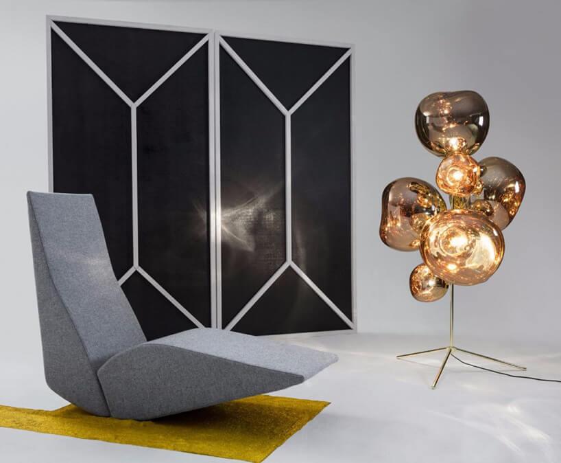 szary fotel na żółtym dywanie obok miedzianej artystycznej dekoracji