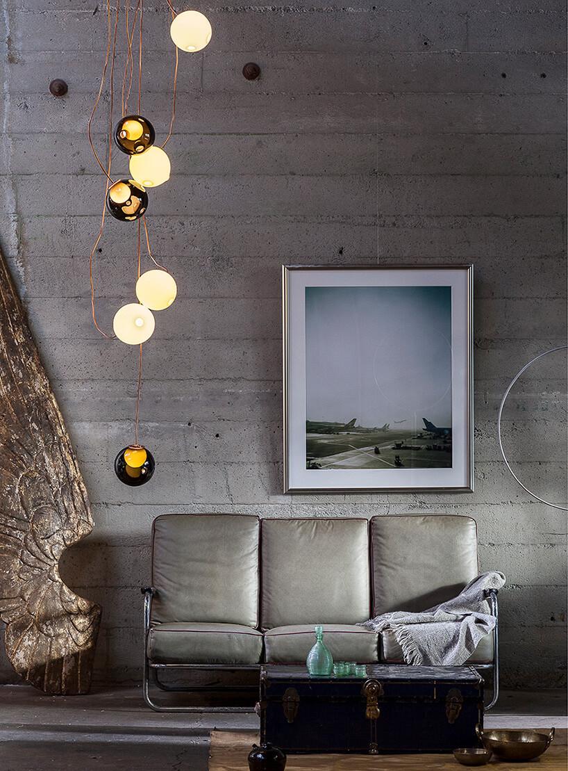 duży obraz wramie nad skórzaną kanapą obok nietypowej lampy