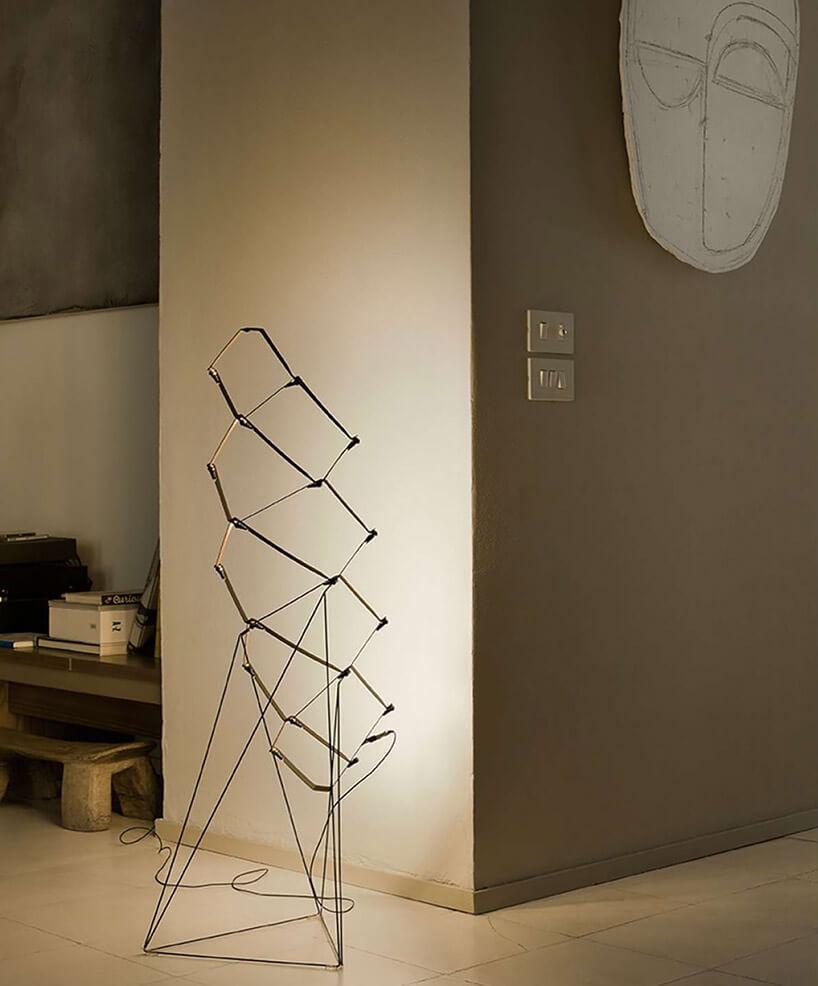 wyjątkowa lampa podłogowa zcienkich drucików na tle jasnobrązowej ściany