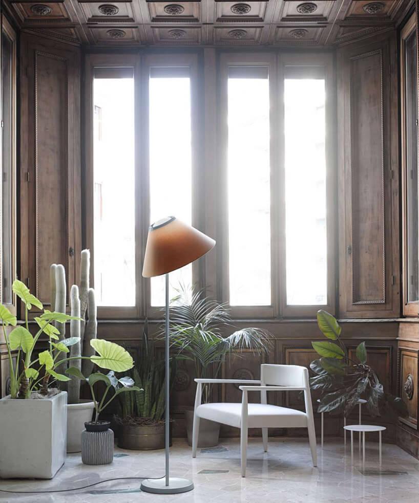 lampa podłogowa zpomarańczowym kloszem obok białego fotela