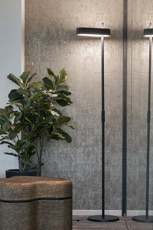 srebrna lampa podłogowa obok pufy iwysokiego kwiatka