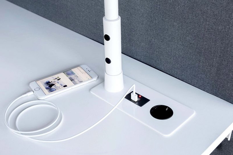 podstawa białej lampy zamontowana wbiałym biurku zgniazdkiem