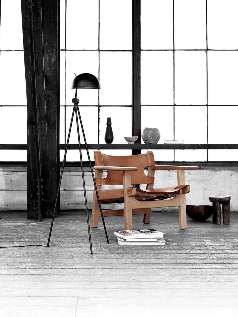 czarna lampa podłogowa waranżacji wnętrza obok brązowego fotela
