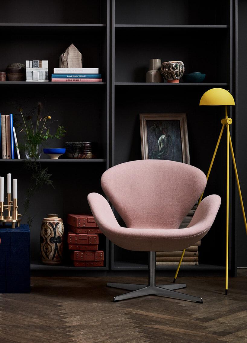 żółta lampa podłogowa wciemnej aranżacji wnętrza obok różowego fotela